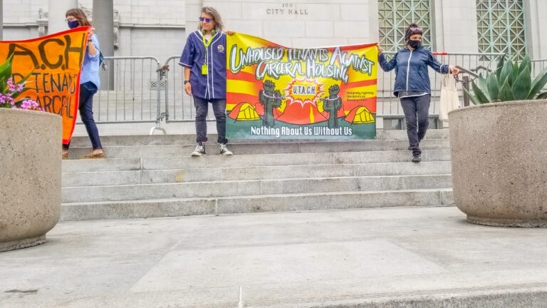 Two organizers hold up a UTACH banner in front of Los Angeles City Hall on May 19, 2021.