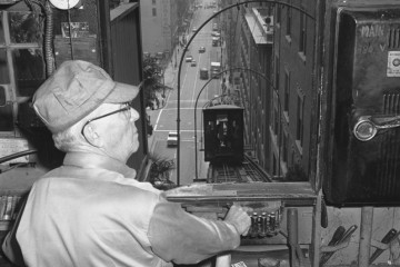 WORKING 'THE ANGEL'-Joseph M. Cooper, 60, operates Angel's Flight, funicular railroad at 3rd and Hill St. His commuters, 5,000 a day, ride the road over its full length, 315 ft., up and down the incline ending at Olive St.